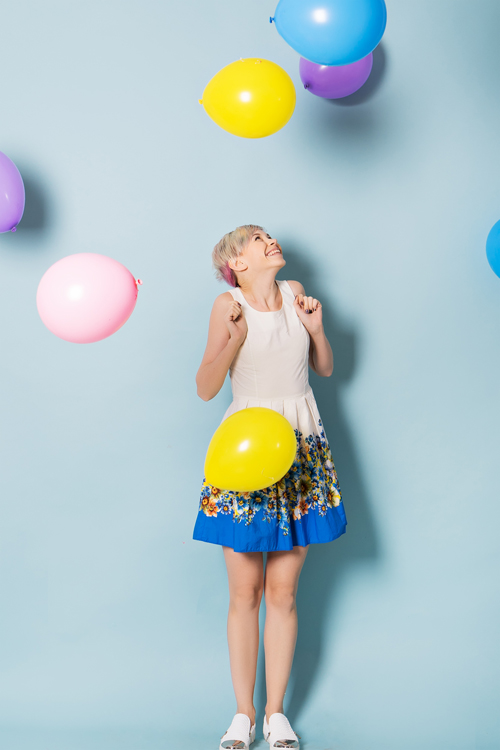 happy cute woman with balloons in studio